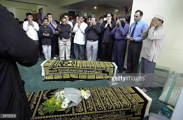 Faithfuls offer prayers infront of the coffins of Iranian twins Ladan and Laleh at Ba'Alwi Mosque in Singapore 09 July 2003 The bodies of Ladan and...