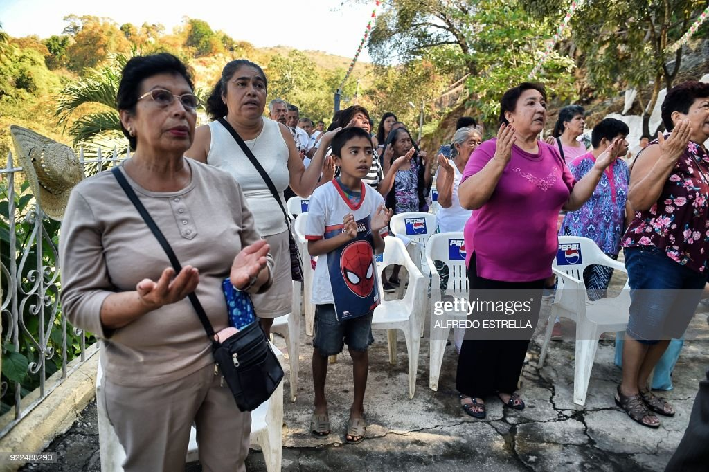 Faithfuls pray during a mass at Kilometro 30 community, near the Acapulco resort in Guerrero State, Mexico, on February 14, 2018. Violence in the state of Guerrero claimed the lives of two priests on February 5, 2018. / AFP PHOTO / Alfredo ESTRELLA / TO