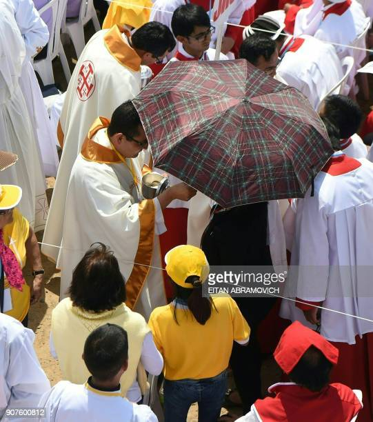 Faithfuls receive communion at an openair mass officiated by Pope Francis at the beach resort town of Huanchaco northwest of the Peruvian city of...