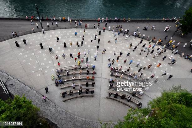 TOPSHOT Faithfuls wearing protective facemasks sit and stand as they follow the social distancing measures at the Grotte de Massabielle in the...