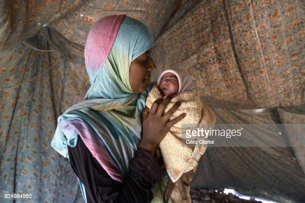Faiza is aged 37 with her daughter Naema just twelve days old when photographed here Faiza now has 6 children and lives with them in the settlement...