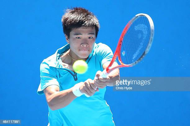 Fajing Sun of China plays a backhand in his second round junior boys' match against Daniil Medvedev of Russia during the 2014 Australian Open Junior...