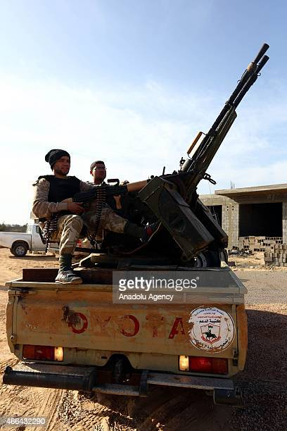 Fajr alLibya forces are seen as they deploy on a check point on a road at the entrance of the city in Sirte Libya on March 15 2015