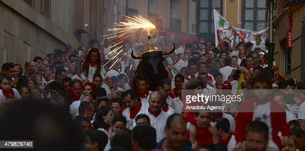 Fake bulls on which lit torches and sparklers had been placed run through the streets after the first bullrun of the San Fermin Festival on July 07...