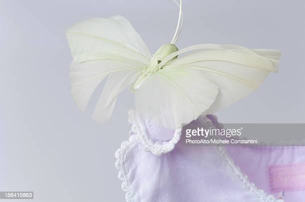 Fake butterfly resting on shoulder of baby clothing