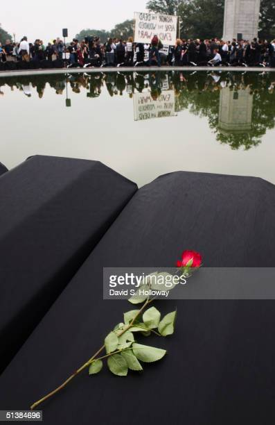 Fake coffins draped in black representing those killed in Iraq sit the near the Women's Memorial during an antiwar protest at Arlington National...