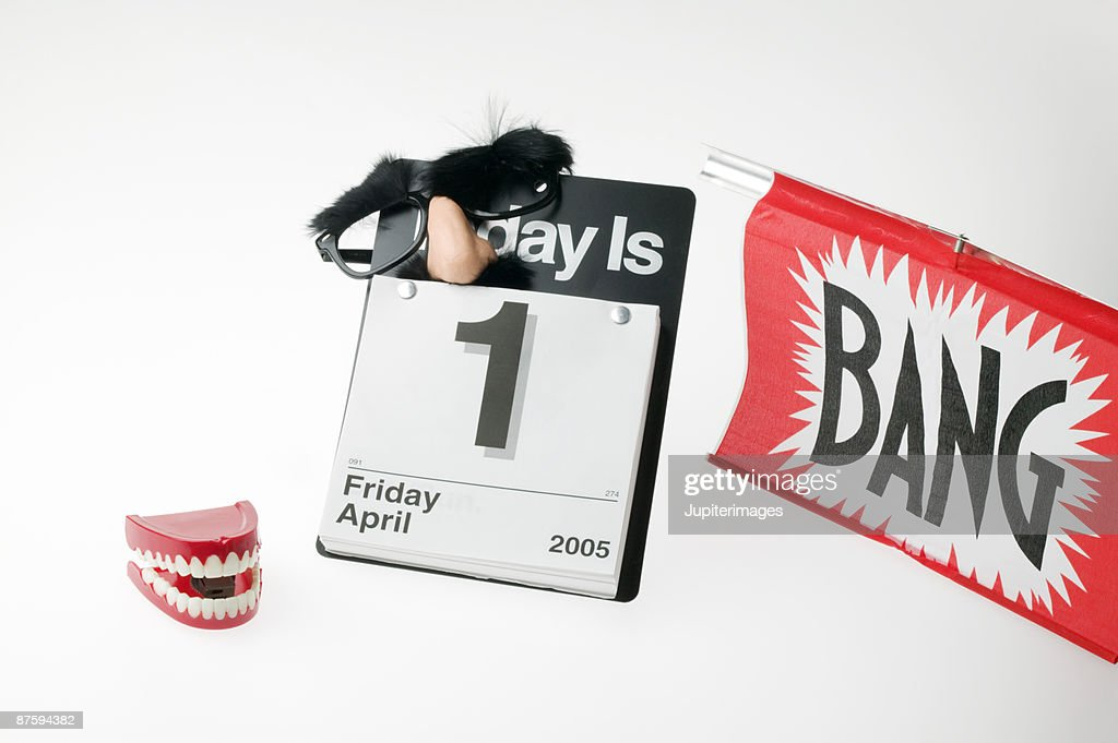 Fake gun, toy teeth, fake nose with glasses and calendar reading April 1st : Stock Photo