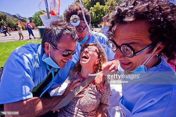 CONTENT] Fake medics pretending to treat a woman in Golden Gate Park at the annual Bay to Breaker footrace and street party festival street party men...