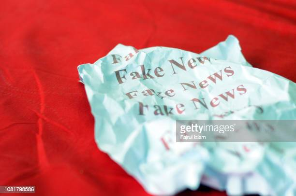 fake news against red background - fake news fotografías e imágenes de stock