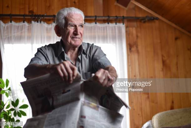 fake news concept of old man tearing apart newspaper , qanon awakening conceptual image - qanon stock pictures, royalty-free photos & images