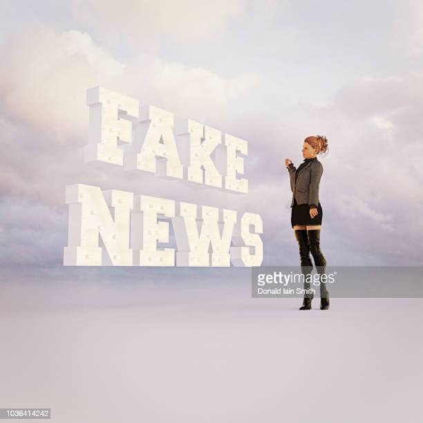 fake news in bright lights with woman watching - fake news fotografías e imágenes de stock