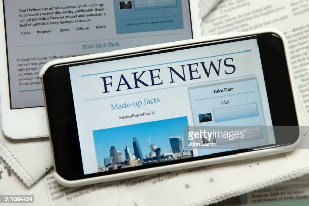 fake news smartphone. - fake news photos et images de collection