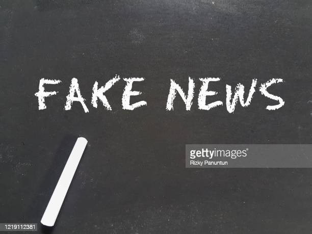 fake news text on blackboard - nepnieuws stockfoto's en -beelden
