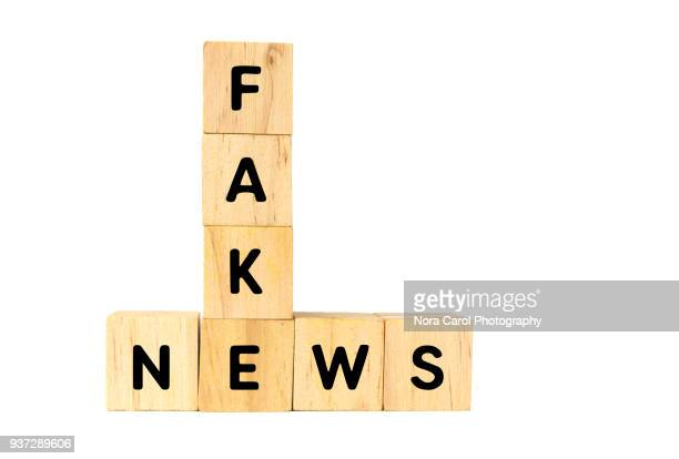 fake news text on wooden blocks on white background - artificial stock pictures, royalty-free photos & images