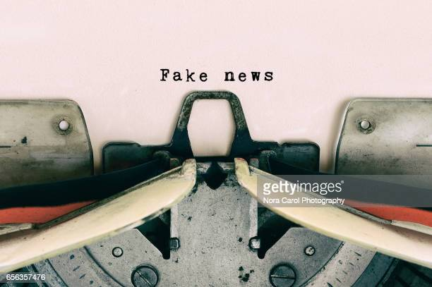 fake news type on vintage typewriter - de media stockfoto's en -beelden