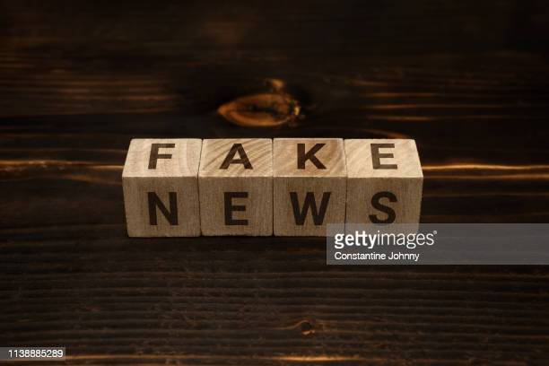 fake news words on wooden blocks - fake news fotografías e imágenes de stock
