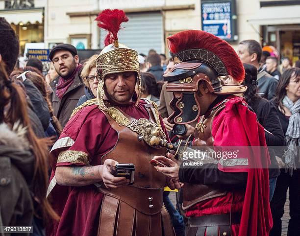 Falso gladiatore romano utilizzando smartphone