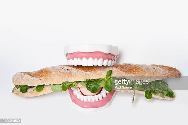 Fake teeth biting into a submarine sandwich