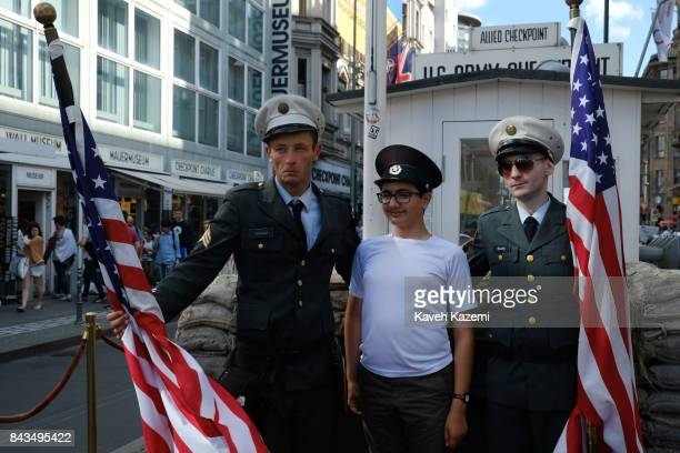 Fake US military men wearing uniforms hold American flags take a souvenir photo with a young tourist boy in exchange for a tip at Checkpoint Charlie...