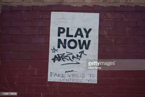 'Fake virus to control you' graffiti on a poster which reads 'Play Now' in central Birmingham under the Coronavirus outbreak on 31st March 2020 in...