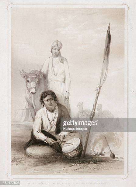 'Fakeer attached to the Suite of the Governor General in Camp' 1844 A bearded Hindu or Muslim holy man sits playing a drum by a small fire Another...