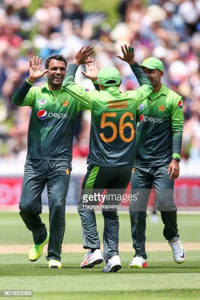 Fakhar Zaman of Pakistan celebrates with Babar Azam and Shadab Khan after taking the wicket of Martin Guptill during game one of the One Day...