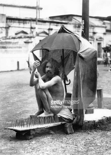 Fakir assis sur un lit de pointes en Inde en 1934