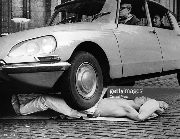 Fakir Mirah Soumak bears the weight of a Citroen DS complete with passengers as it drives over his stomach in the Grande Place Brussels Belgium