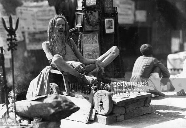A fakir rests on a bed of nails in a display of public penance in Calcutta India c1930