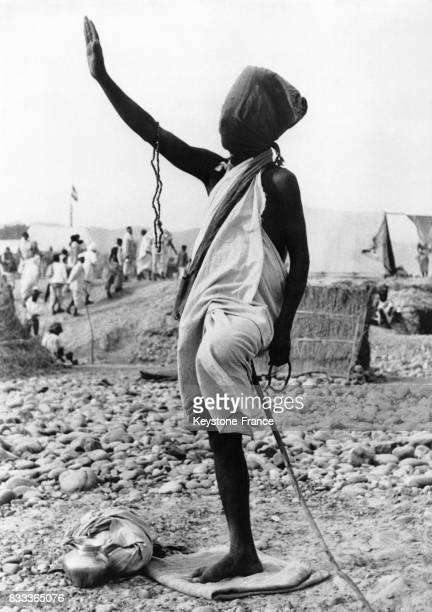 Fakir se tenant sur une jambe appuyé sur une épée le bras levé et un sac sur la tête en Inde
