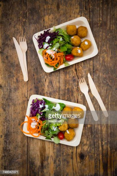 Falafel and salad on wooden disposable plates and cutlery