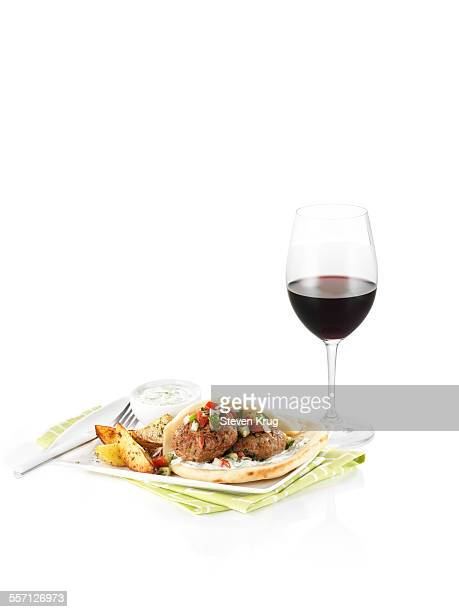 Falafel pita with potatoes and glass of red wine