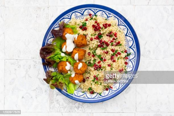 falafel with tabbouleh salad on a plate - larissa veronesi stock-fotos und bilder