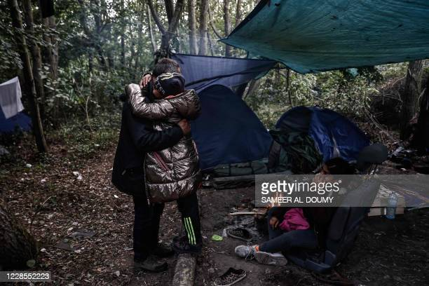 Falah, an Iraqi migrant hugs his daughter Arwa after getting her ready to be smuggled into Britain at a makeshift migrants camp in Dunkirk, northern...