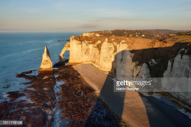 falaise d'aval, with aiguille rock formation and natural arch at at warm sunset light. les falaises d'etretat, aiguille d'etretat, etretat, seine-maritime department, normandy, france - 炭酸石灰 ストックフォトと画像