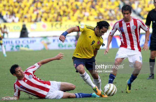 Falcao Garcia of Colombia fights for the ball with Ivan Piris and Victor Caceres of Paraguayduring a match between Colombia and Paraguay as part of...