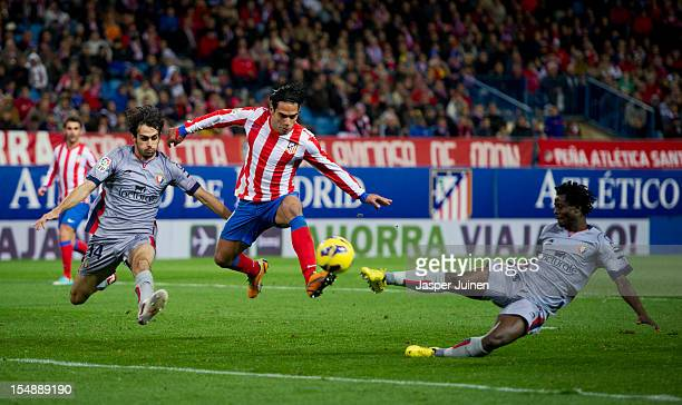 Falcao of Club Atletico de Madrid duels for the ball with Anthony Annan and Alejandro Arribas of Osasuna during the La Liga match between Club...