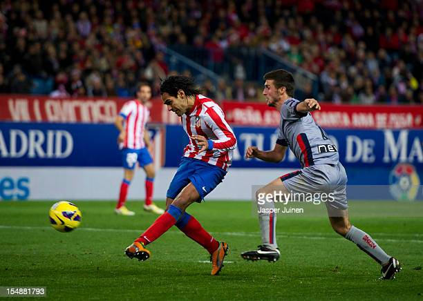 Falcao of Club Atletico de Madrid strikes to score besides Oier Sanjurjo of Osasuna during the La Liga match between Club Atletico de Madrid and CA...