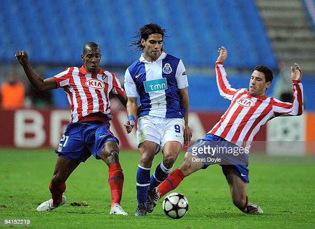 Falcao of FC Porto is tackled by Luis Parea and Maxi Rodriguez of Atletico Madrid during the UEFA Champions League Group D match between Atletico...