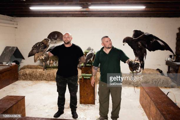 Falconers Holding Birds of Prey