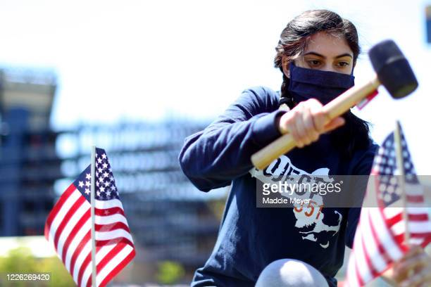 Faleehah Dam of Foxborough plants a flag outside of Gillette Stadium on May 21 2020 in Foxborough Massachusetts The Patriots foundation partnered...
