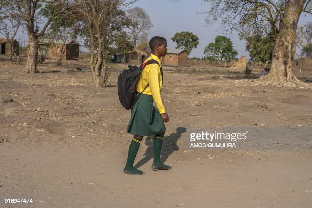 Falesi Samuel a Form Four Student at Atsikana Pa Ulendo Girls Secondary School walks through a rural area during her visit to the village from school...