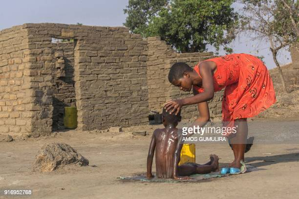Falesi Samuel a Form Four Student at Atsikana Pa Ulendo Girls Secondary School bathes a child during a visit to her village on the outskirts of...