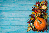 Fall border of apples, berries, pumpkins on blue table, copy space