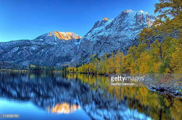 Fall colors and snow capped peaks line Silver Lake in the Eastern Sierra, California.