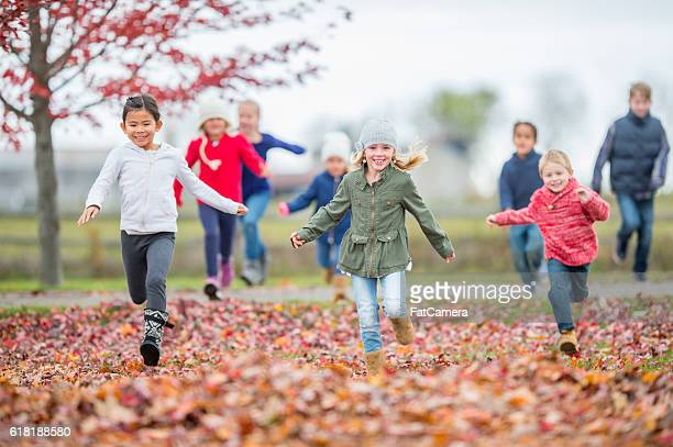 fall time - kids playing tag stock photos and pictures