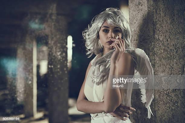 Fallen angel smoking a cigar in a ruin.