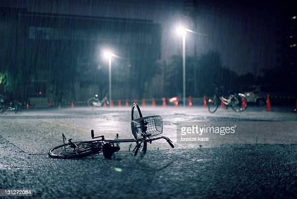 Fallen bicycle in heavy rain.