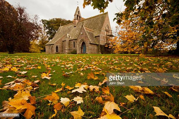 Fallen Leaves On The Grass In Front Of A Church In Autumn; Northumberland England