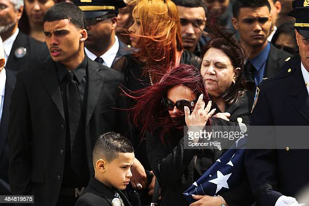 Fallen New York Police Department officer Dennis Guerra's wife Cathy and one of his four children stand outside of Rose of Lima Church in Far...